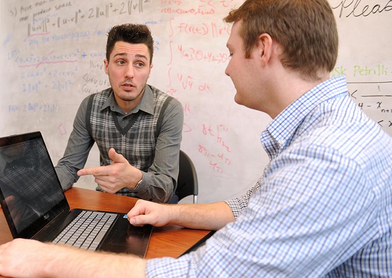 Mathematics student speaking with professor at Adelphi